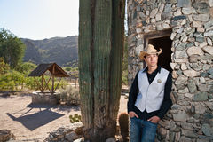 Cowboy Deputy Sheriff. Young deputy sheriff cowboy leaning against an old block building. Saguaro cactus and an old well are off to the side of him royalty free stock photography