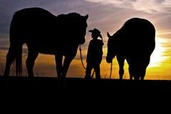 Cowboy, der mit Pferden steht Lizenzfreie Stockbilder