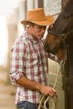 Cowboy, der Pferd flüstert Stockbild