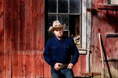 Cowboy an der Scheune, die Gürtelschnalle ernst hält Lizenzfreie Stockfotos