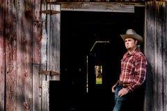 Cowboy in der Scheunen-Tür, die in Richtung Sun blickt Lizenzfreies Stockfoto