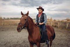 Cowboy die een paard in westelijke woestijnvallei berijden, stock foto's