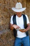 Cowboy die het aanrakingsscherm van tabletcomputer met behulp van stock fotografie