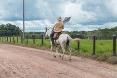 Cowboy die op het landbouwbedrijf berijden stock foto