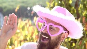Cowboy divertente con gli occhiali da sole divertenti di rosa dei pantaloni a vita bassa ed il cappello rosa comico Faccia il fro video d archivio