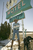 Cowboy with dog stand in front of Sands Motel sign with RV Parking for $10, located at the intersection of Route 54 & 380 in Carri Royalty Free Stock Photo