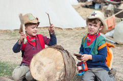 Cowboy drummer. Three year old twin boys play with  sticks sitting on the ground Stock Photo