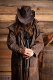 Cowboy duster long hair rifle look down wall. A cowboy holding on to he weapon with his head down royalty free stock images