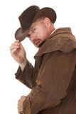 Cowboy duster look back touch hat close. A cowboy in his duster touching the brim of his hat royalty free stock photo