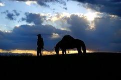 Cowboy en pakpaard, silhouet Royalty-vrije Stock Afbeeldingen