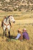 Cowboy et cow-girl s'asseyant dans l'herbe tenant le cheval Image stock