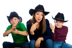 Cowboy family with fake finger guns. A pretty Mom and her two sons wearing cowboy hats and pointing imaginary guns with their fingers Royalty Free Stock Image