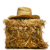 Cowboy Farmer Straw Hat on Hay Bale over White. Cowboy farmer traditional hat on top of a bale of straw hay over white stock photo