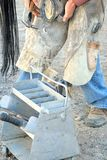 Cowboy farrier working. Cowboy farrier working on a horseshoe on the ranch outdoors Royalty Free Stock Photo