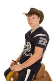 Cowboy in football jersey sitting on saddle Royalty Free Stock Photo