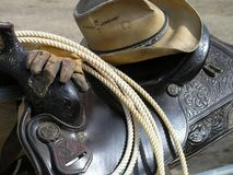 Cowboy Gear. Western saddle, hat, work gloves and rope Stock Photography