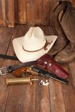 Cowboy Gear. A cowboy hat, black powder pistol, and boots on a wooden background stock photos