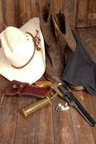 Cowboy Gear. A cowboy hat, black powder pistol, and boots on a wooden background stock image