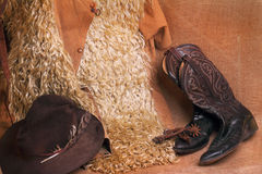 Cowboy Gear. Western antique angora woolly cowboy chaps, old worn hat with mangled feather, boots and rusty spurs against burlap. Possible western flyer Stock Images
