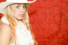 Cowboy girl. With hat on red rose background Royalty Free Stock Photos