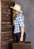 Cowboy girl or pretty woman in stylish hat and blue plaid shirt holding gun and old suitcase Royalty Free Stock Photography