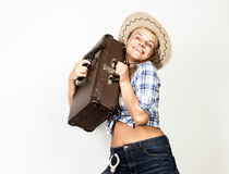 Cowboy girl or pretty woman in stylish hat and blue plaid shirt holding gun and old suitcase Stock Image