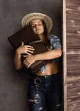 Cowboy girl or pretty woman in stylish hat and blue plaid shirt holding gun and old suitcase stock photography