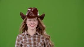 Cowboy girl sends an air kiss to her boyfriend. Green screen. Slow motion stock video footage