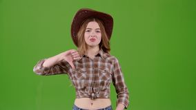 Cowboy girl is showing her finger down. Green screen