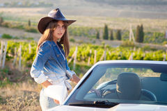 Cowboy girl stands at the convertible Royalty Free Stock Photo