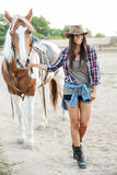 Cowboy girl taking her horse for a walk. Full length portrait of a girl taking her horse for a walk at the farm royalty free stock images