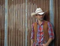 Cowboy Glances. A cowboy leans against a metal wall Stock Photos