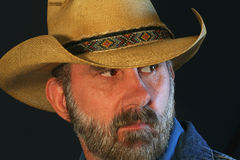 A Cowboy Glances Over His Shoulder. A Bearded Cowboy Against Black Glances Over His Shoulder Stock Photography