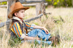 Cowboy on a grass at an old fence Royalty Free Stock Images