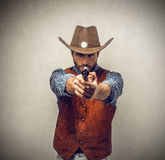 Cowboy with a gun. Serious and scary cowboy holding a gun ready to shoot Royalty Free Stock Image