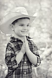 Cowboy Hands Together. A portrait of a young five year old boy dressed like a cowboy plotting his next move.  His hands are together and he is smiling thinking Stock Photography