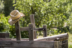 Cowboy Hat. A straw cowboy hat hanging from a post on an old wood wagon royalty free stock photo