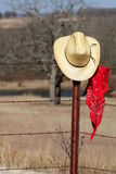 Cowboy Hat and Bandana. A yellow straw cowboy hat hangs on a rusty barbed wire fence post with a red bandana hanging beside it, in a country field with trees and stock photography