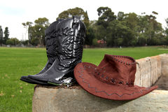 Cowboy hat and boots. Brown Cowboy hat and black boots on old cement water dam stock image