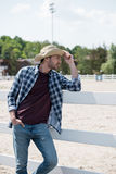 Cowboy in hat and checkered shirt looking away and leaning on fence at ranch. Handsome cowboy in hat and checkered shirt looking away and leaning on fence at royalty free stock images