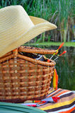 Cowboy hat, fishing tackle, towels and wicker basket, nature Royalty Free Stock Image