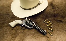 Cowboy Hat and Gun. Cowboy hat and a old western revolver on top of a deer skin Royalty Free Stock Photo