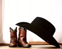 Cowboy hat leaning on small boots Stock Photos