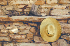 Cowboy hat and old boots. Torn old cowboy hat and boots on a stone wall background stock photo