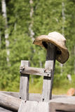 Cowboy Hat On Post. A straw cowboy hat resting on an old wooden post on an old kitchen wagon royalty free stock photos