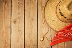 Cowboy hat with red bandanna on wooden rustic background. View from above Royalty Free Stock Image
