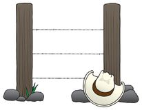Cowboy Hat on the Rocks. Two fence posts with barbed wire running between them and a cowboy hat on the rocks in front of them Stock Photo