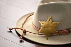 Cowboy hat with Sheriff badge. On wooden background in horizontal format with selective focus Royalty Free Stock Image