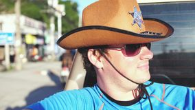 Handsome cowboy in sheriff hat and sunglasses traveling in a pickup truck in sunny day. slow motion. 3840x2160. Cowboy in hat and sunglasses traveling in a stock video footage