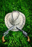 Cowboy hat and two guns. Dirty Cowboy hat and two guns on the green grass stock photos